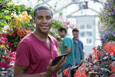 Commercial organic plant nursery growing organic flowers. Man working,using a digital tablet