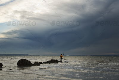 A man stands on a rock in the middle of the Puget Sound with his sea kayak floating next to him.