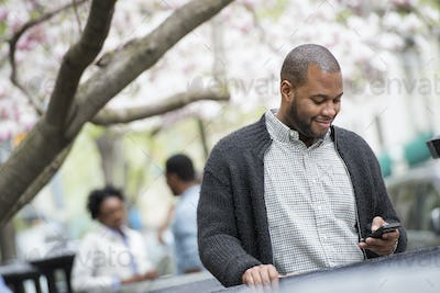 Spring in the city,A young man checking his phone and texting. A couple in the background