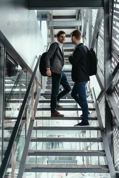 Two men going up, down stairs while chatting