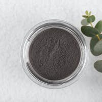 Black cosmetic clay powder for skin and hair