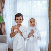 two children greeting wearing muslim white ihram