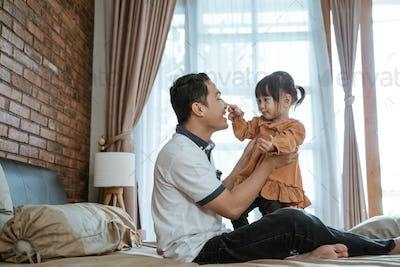 father laughed happily when his nose was touched by the little girl