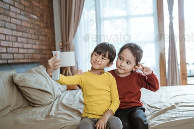 two little girls smile while taking a selfie together with a smartphone