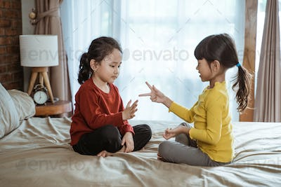 two little asian girls smiled happily playing rock paper scissors