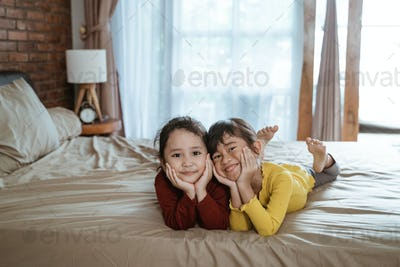 happy two little girls lying on the bed