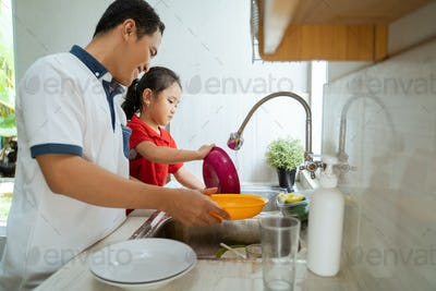 Daughter helping her father wash dishes