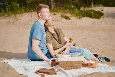 Picnic on beach with food and drinks. Young boy and girl sunbathing