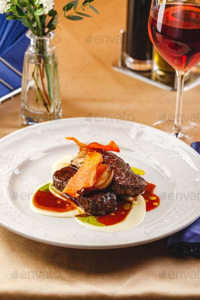 Beef tenderloin medallions with sauce and onion