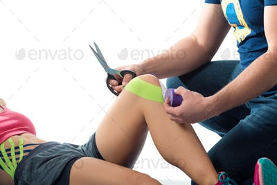 A man cuting kinesio bright tapes on the woman's knee