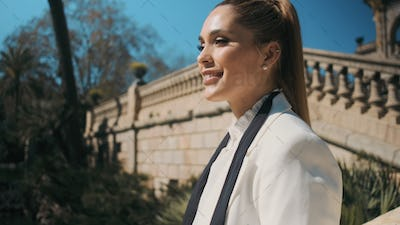 Close up beautiful elegant woman in classic white suit happily looking away in old park