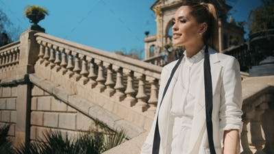 Portrait of beautiful elegant woman in classic white suit confidently looking away in old park