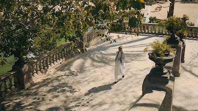 Top view of gorgeous elegant woman in white suit walking through old beautiful park