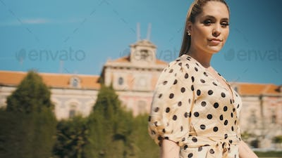 Young beautiful woman in polka dot dress confidently looking in camera walking along park