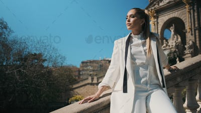 Elegant woman in classic suit confidently posing on stairs in park with old beautiful architecture