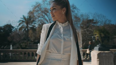 Portrait of young posh woman in classic suit confidently posing on camera in beautiful park