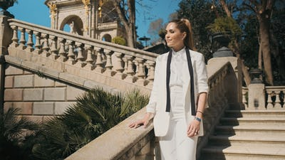Young gorgeous woman in classic white suit standing on stairs in old beautiful city park