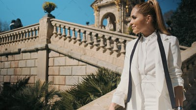 Young gorgeous woman in classic white suit confidently walking down the stairs in old park