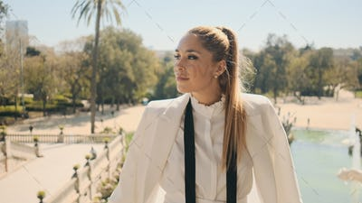 Portrait of young gorgeous woman in stylish white suit posing with beautiful view on park