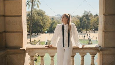 Gorgeous woman in stylish white suit standing on old balcony with amazing view on park