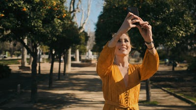 Young beautiful woman taking photo on smartphone during walk along cozy city park