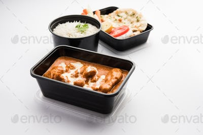 Paneer Butter Masala in black plastic container, ready for home delivery