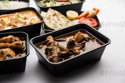Online food delivery concept for Indian Restaurant showing plastic containers with food