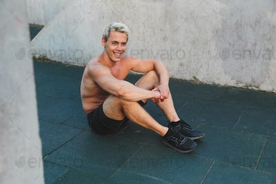 Young caucasian athlete man sitting on work out area outdoors