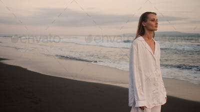 Attractive girl walking by the ocean at dusk. Beautiful model resting on paradise island