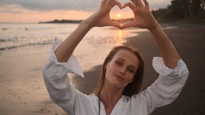 Portrait of beautiful girl dreamily showing heart gesture over sunset by the ocean on island