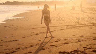 Beautiful slim girl in swimsuit meeting sunset by the ocean. Attractive model posing on beach
