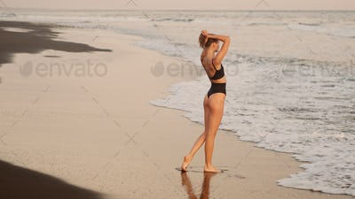 Gorgeous girl in black swimsuit dreamily resting by the ocean on tropical island
