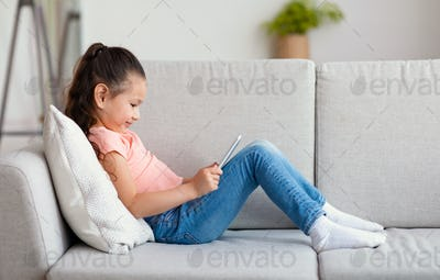 Asian Girl Using Mobile Phone Watching Cartoons At Home