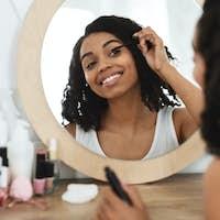 Daily Makeup. Beautiful Black Woman Applying Mascara On Eyelashes At Home