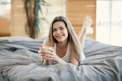 Happy young girl drinking coffee while lying on bed in morning