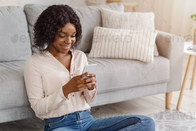 Online Communication. Happy black girl texting on cellphone while sitting on floor
