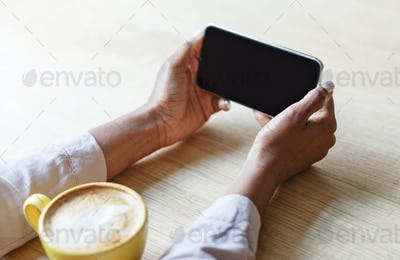 Cropped view of young woman holding smartphone with blank screen while drinking coffee at cafe