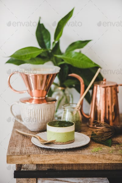 Green matcha cheesecake dessert and black coffee in copper pot