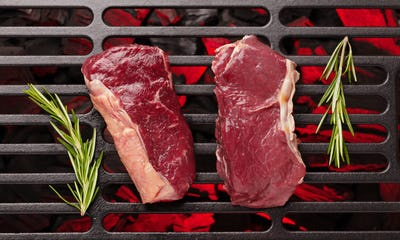 Raw beef steak cooking on grill