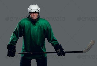 Hockey player holds gaming stick.