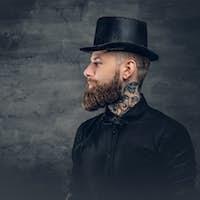 Brutal bearded male over grey background.