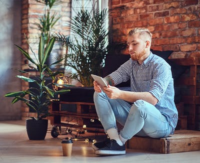 The full body image of blond stylish male using a tablet PC.