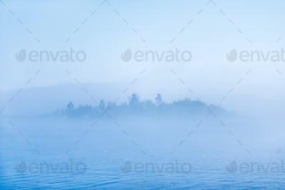 Pond or lake with fog and blurred island.