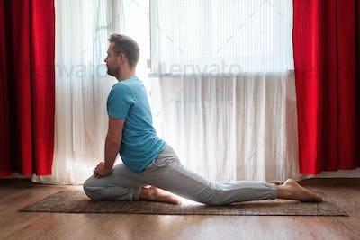man doing asana one legged king pigeon or eka pada rajakapotasana