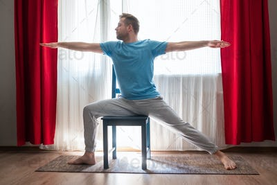 Caucasian young man in Warrior 2 Pose using chair at his living room