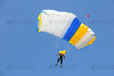 Skydiver under canopy of yellow with blue parachute in cloudless sky