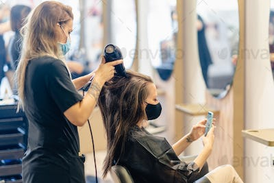 Hairdresser drying her client's hair with a hairdryer wearing protective masks in a beauty