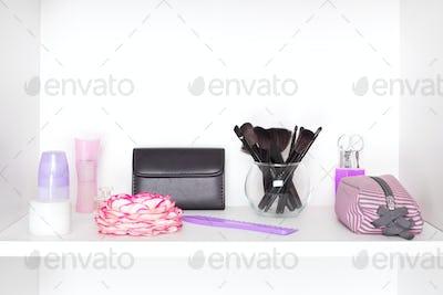 Beauty products and accessories on white shelf inside closet