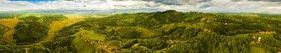 Aerial panorama of of green hills and vineyards with mountains in background
