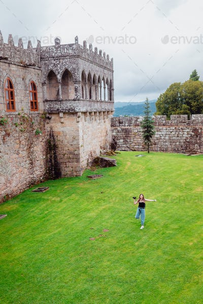 Young female tourist running on grass with a castle on the background